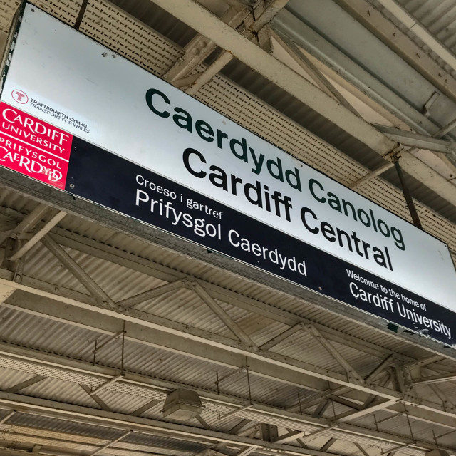 """Bilingual station name sign at Cardiff Central railway station. The sign is sponsored by Cardiff University."" stock image"