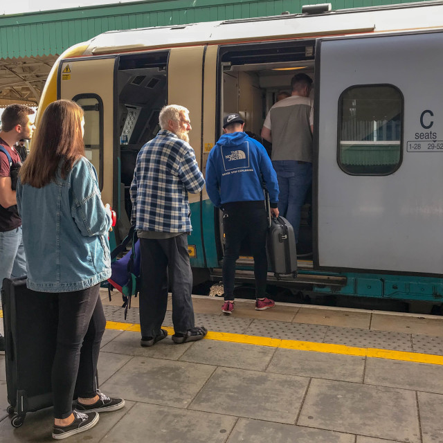 """Passengers boarding a commuter train at Cardiff Central station."" stock image"