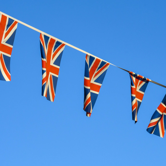 """""""Row of small Union Jack flags against a deep blue sky."""" stock image"""