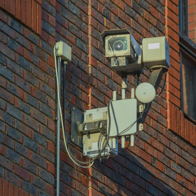 """Remote controlled CCTV camera mounted on a wall"" stock image"