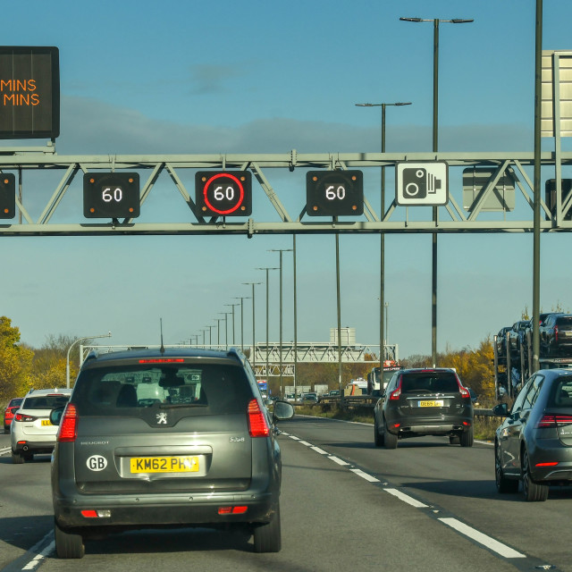"""Traffic passing under variable speed limit signs on the M4 motorway near Bristol."" stock image"