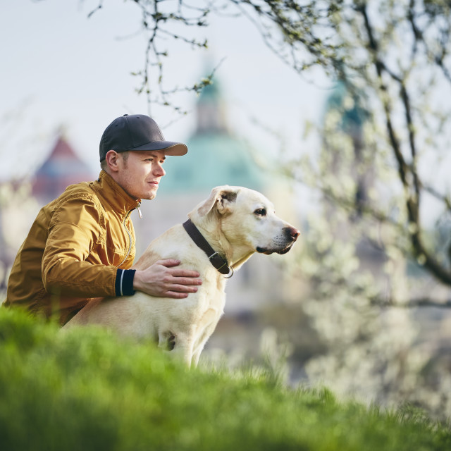"""""""Young man relaxation with dog in public park"""" stock image"""
