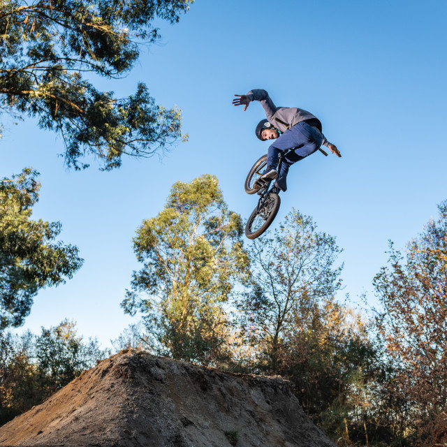 """BMX Bike jump over a dirt trail"" stock image"