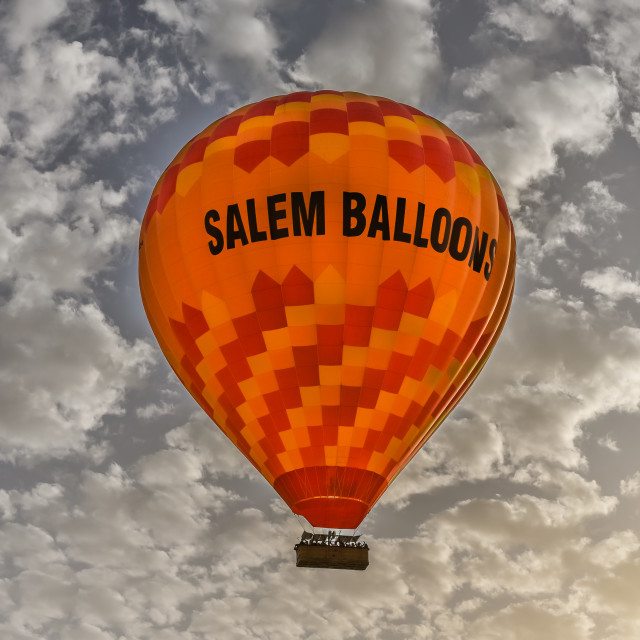 """An orange hot-air balloon in the sunrise"" stock image"