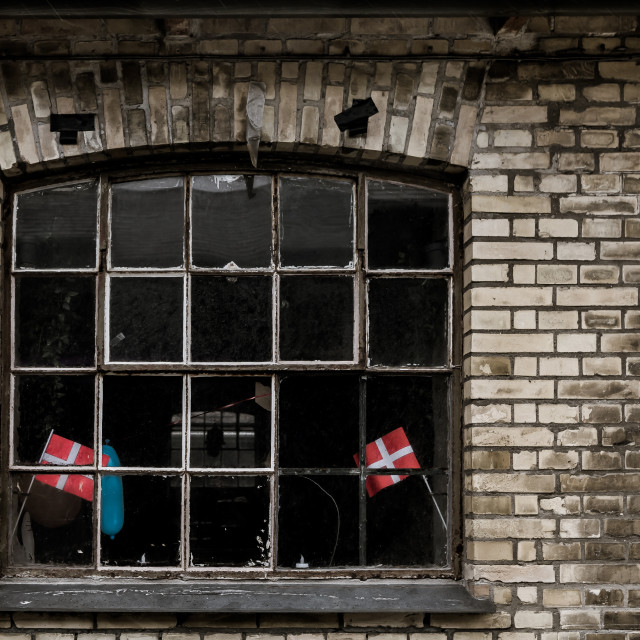 """Danish flags and a blue balloon in an ancient factory window"" stock image"