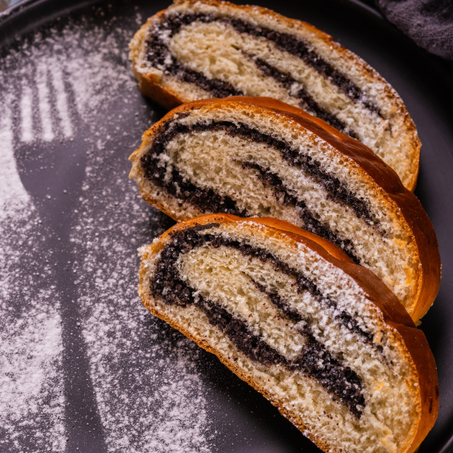 """""""Poppy seed strudel on dark plate with silhouette of fork made by sugar"""" stock image"""