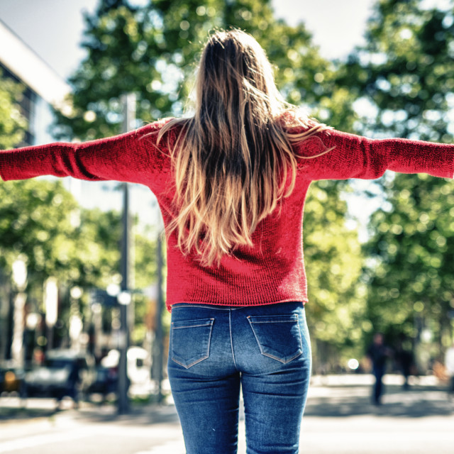 """""""Back view of blonde girl with open arms symbolically embracing the city"""" stock image"""