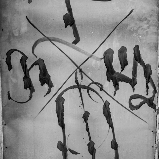 """Strange black symbols on abandoned glass door"" stock image"