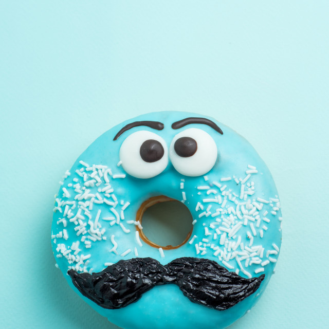 """Blue glazed donut with mustache flying"" stock image"