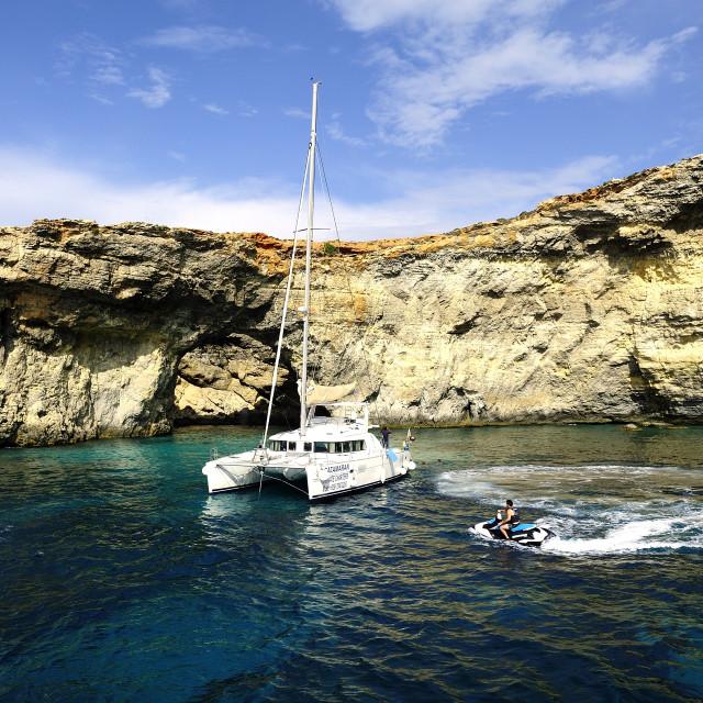 """Catamaran at anchor below the cliffs of Comino"" stock image"
