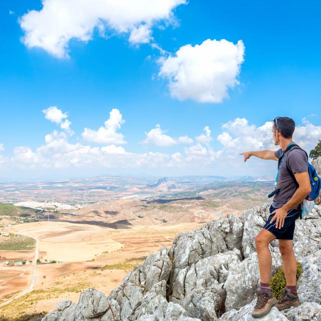 """""""Man pointing the horizon on rocky mountain"""" stock image"""