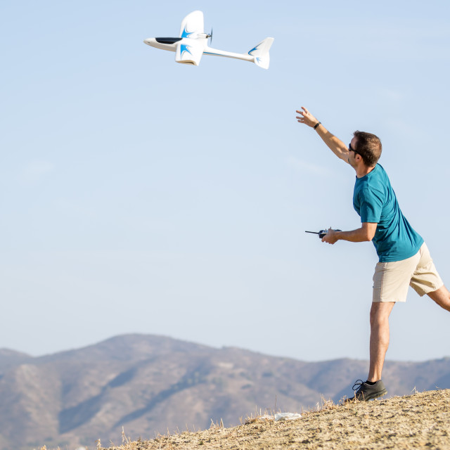 """""""Young man setting remote control plane in air"""" stock image"""