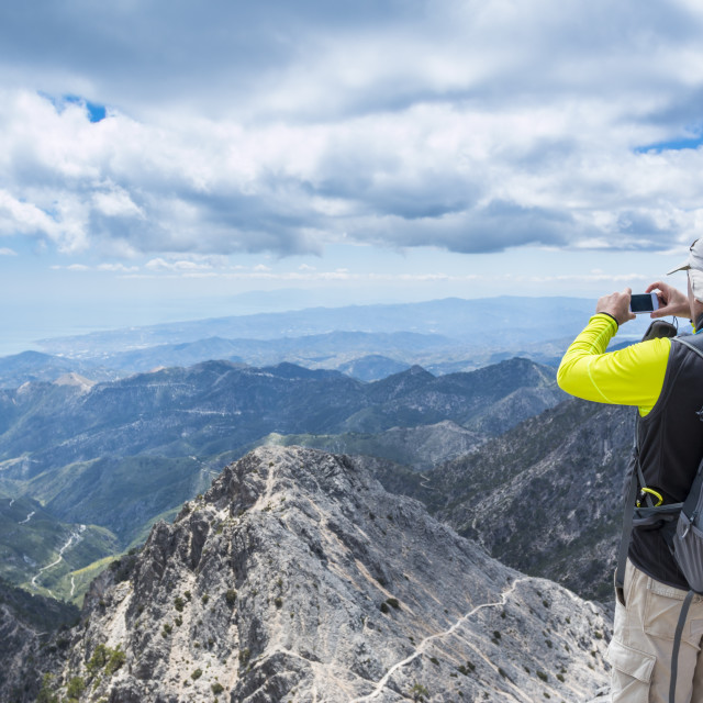 """""""Hiker man taking pictures of mountains"""" stock image"""