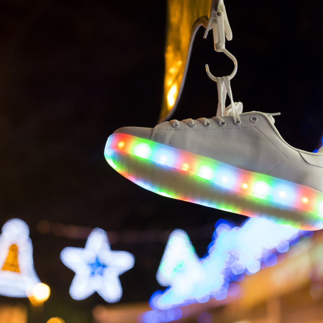 """""""Sportive shoe hanging on blurred background of lights in dark"""" stock image"""