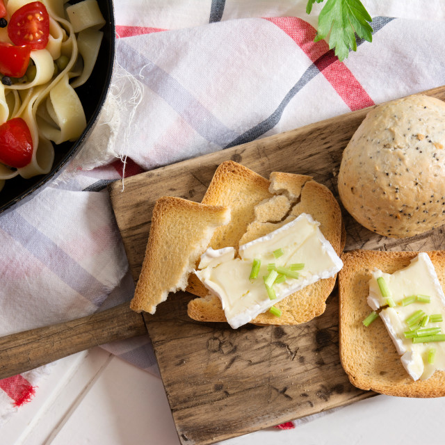 """toasted bread, with brie cheese and chives and tagliatelle with cherry tomatoes"" stock image"