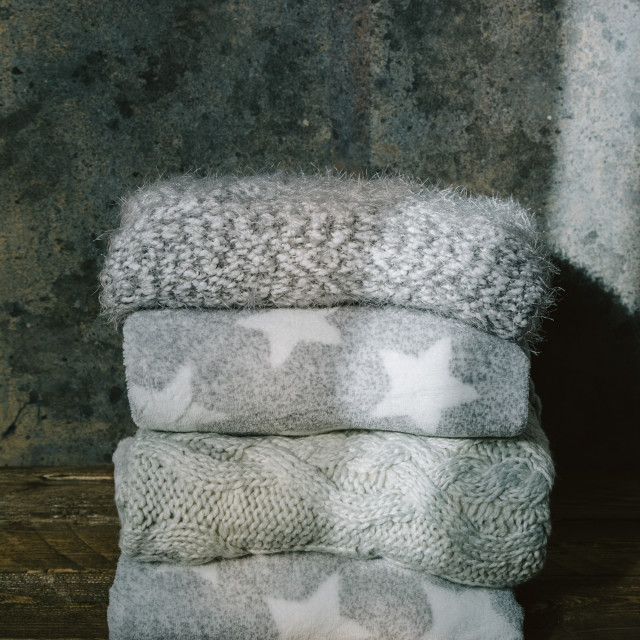 """Pile of knitted winter clothes on wooden background, sweaters, knitwear, in a..."" stock image"