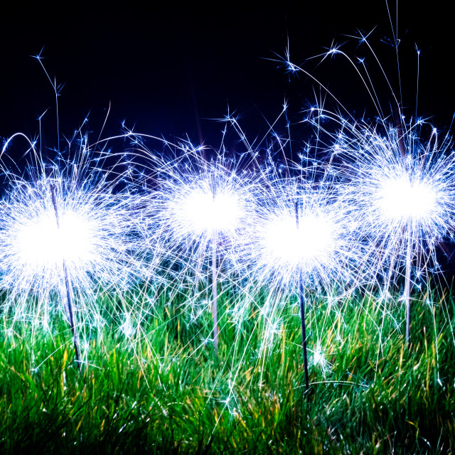 """Blue sparklers in the grass"" stock image"
