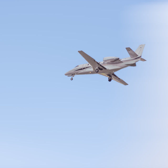 """Private jet flying in the blue sky"" stock image"