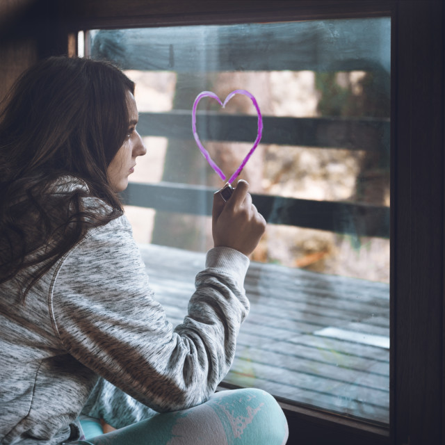"""Young woman drawing a heart on the window"" stock image"