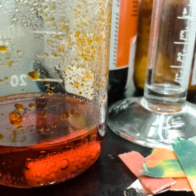 """""""Orange chemical reaction inside a glass beaker"""" stock image"""