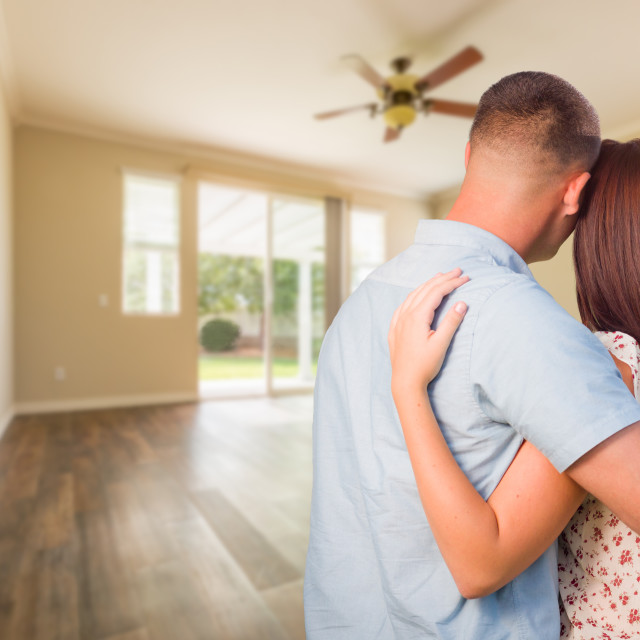 """Young Military Couple Looking At Empty Room of New House"" stock image"