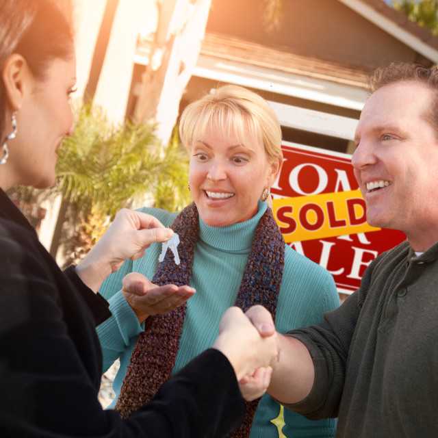 """Hispanic Female Real Estate Agent Handing Over New House Keys to Happy Couple..."" stock image"