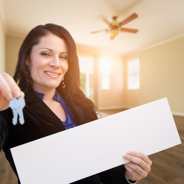 """Hispanic Woman With House Keys and Blank Sign In Empty Room of House"" stock image"