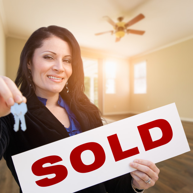 """Hispanic Woman With House Keys and Sold Real Estate Sign In Empty Room of House"" stock image"