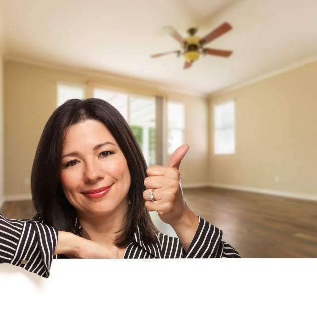 """Hispanic Woman with Thumbs Up In Empty Room of House"" stock image"