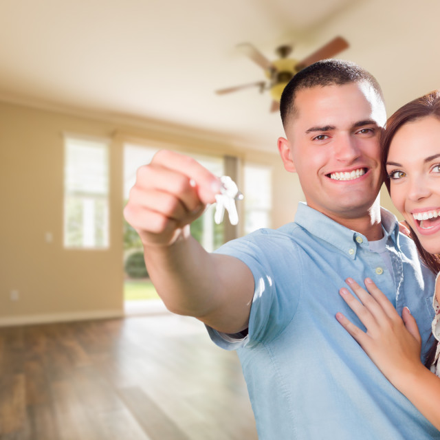 """Young Military Couple with House Keys In Empty Room of New Home"" stock image"
