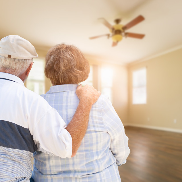 """Senior Couple Looking Into Empty Room of House"" stock image"