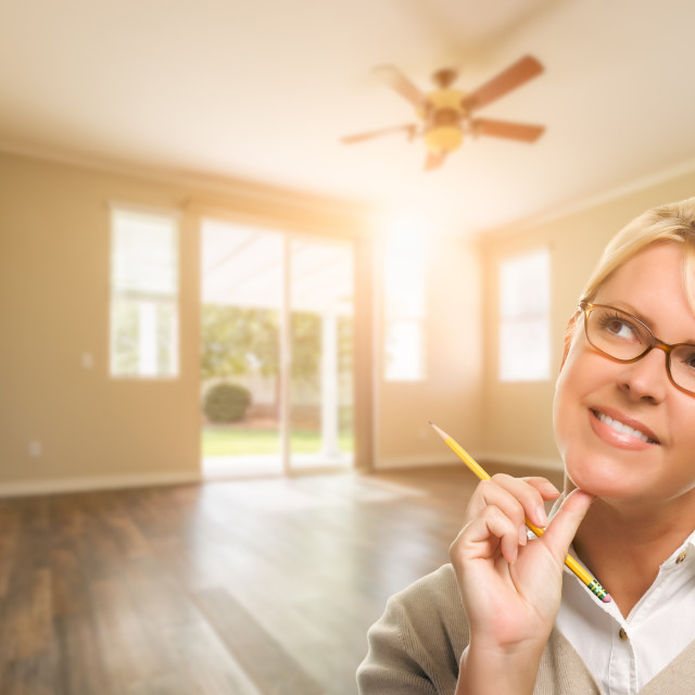 """Attractive Woman with Pencil In Empty Room of House"" stock image"