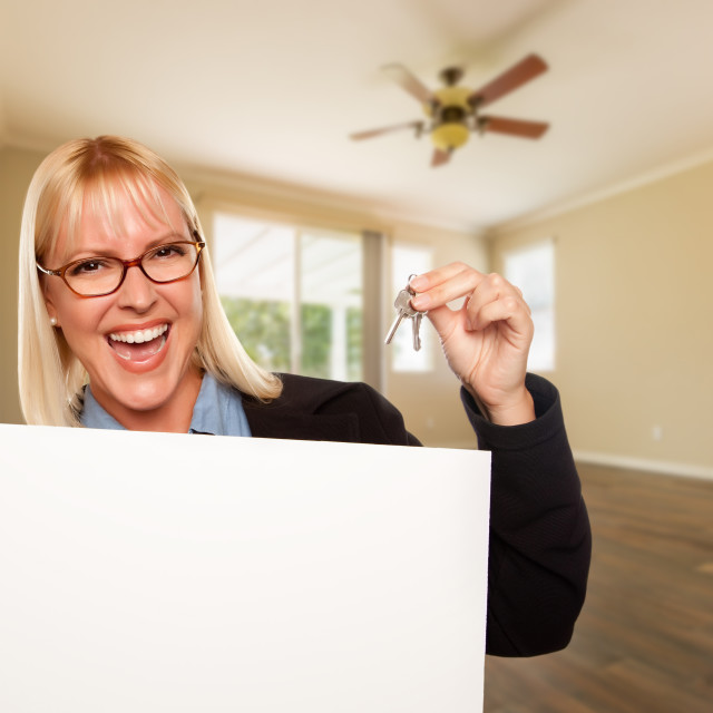 """Attractive Young Woman with New Keys and Blank Board In Empty Room of House"" stock image"