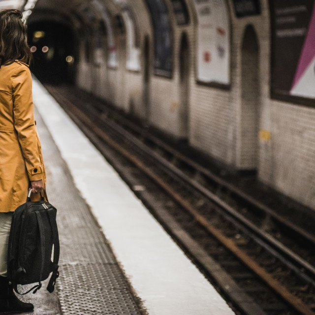 """""""Woman in Yellow Waiting on a Train"""" stock image"""