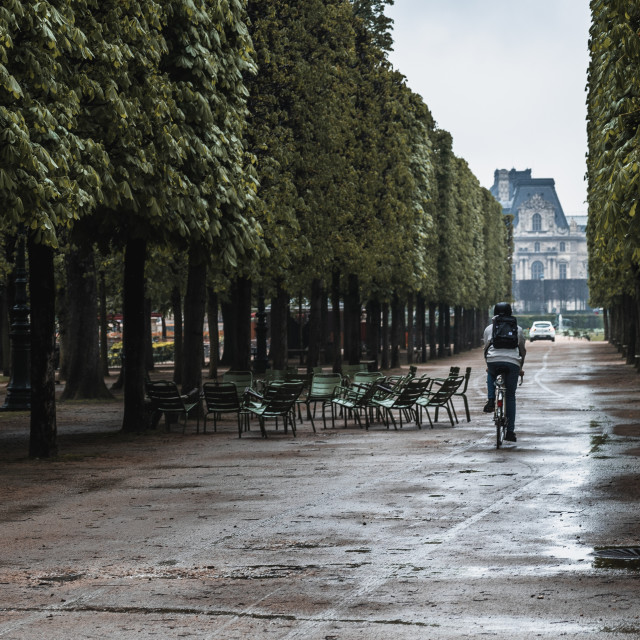 """""""A cyclist rides through the park in Paris after the rain"""" stock image"""