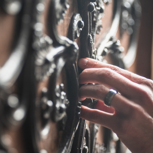 """""""A hand touches the doors of Notre Dame Cathedral"""" stock image"""