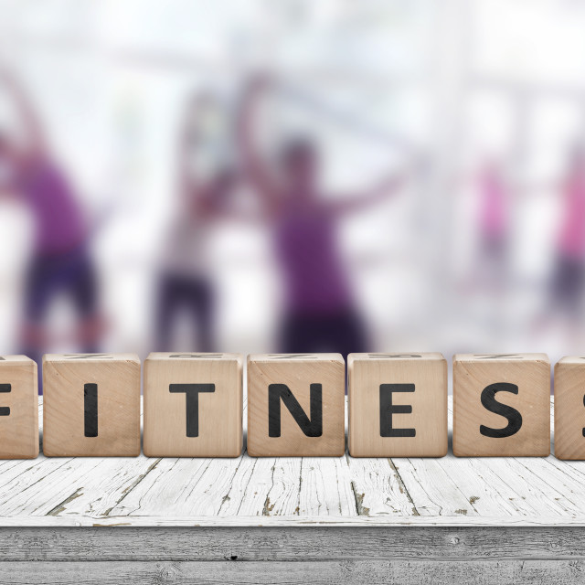 """""""Fitness sign on a table in a gym with women"""" stock image"""