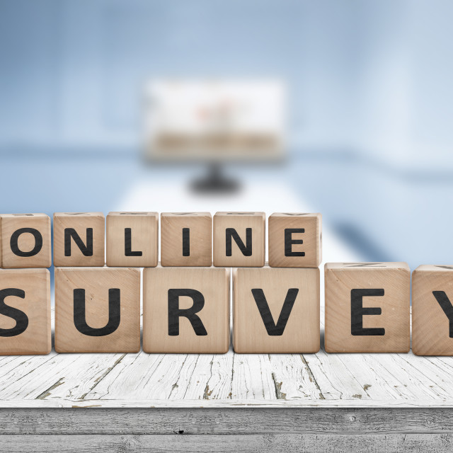 """""""Online survey sign on a table in a blue room"""" stock image"""