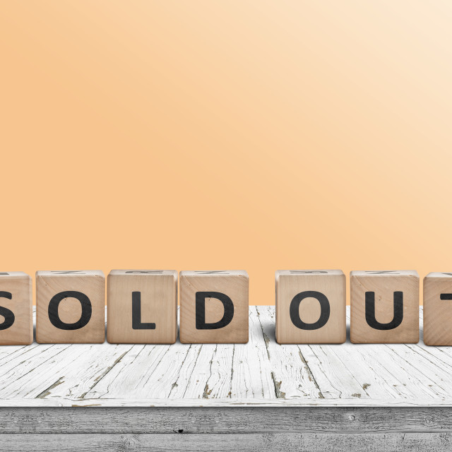 """Sold out sign on a wooden table with a yellow wall"" stock image"