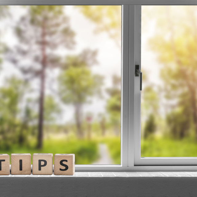 """Tips sign in a window with a view to a green garden"" stock image"