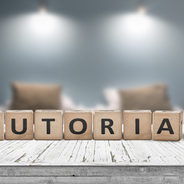 """Tutorial sign on a wooden table in a room with lights"" stock image"