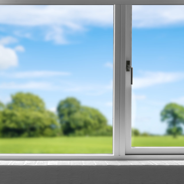 """View from a closed window to a green meadow"" stock image"