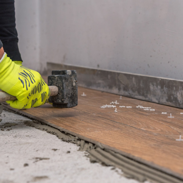 """""""Worker placing ceramic floor tiles on adhesive surface, leveling"""" stock image"""