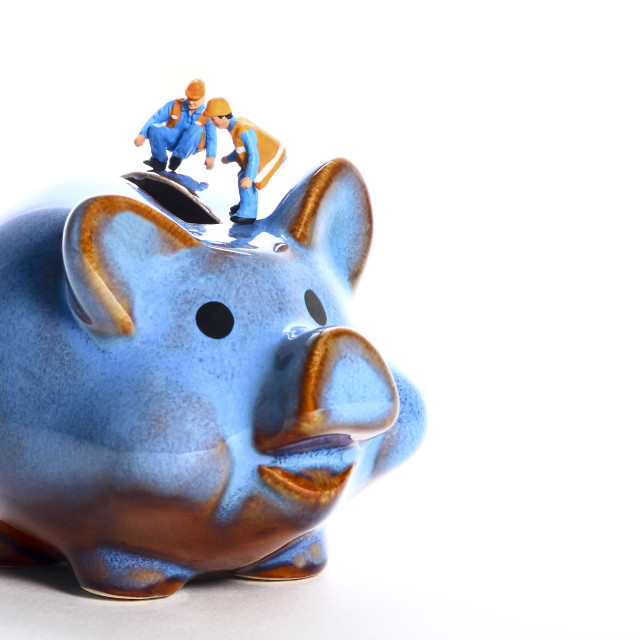 """""""Conceptual diorama image of miniature figure workmen peering in to a piggy bank money box"""" stock image"""