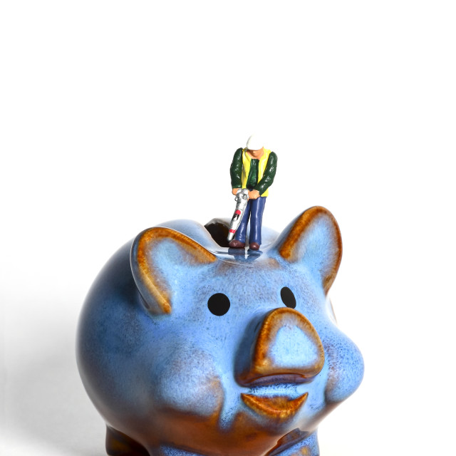 """""""Conceptual diorama image of miniature figure with a road drill trying to open a piggy bank"""" stock image"""