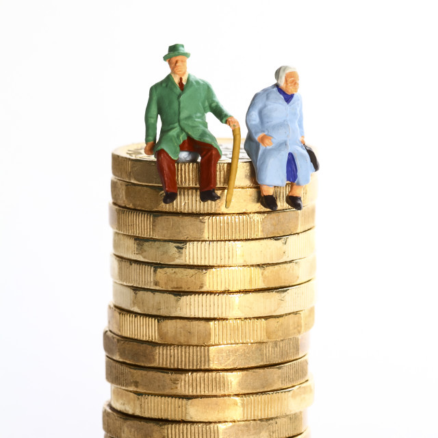 """""""Conceptual diorama image of a miniture figure retired couple sat on a stack of pound coins"""" stock image"""