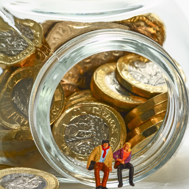 """""""Conceptual diorama image of miniature figures sat on a glass jar filled with pound coins"""" stock image"""