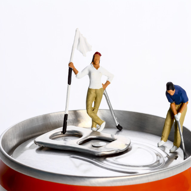 """""""Conceptual diorama image of a miniture figure couple playing golf on a drinks can"""" stock image"""