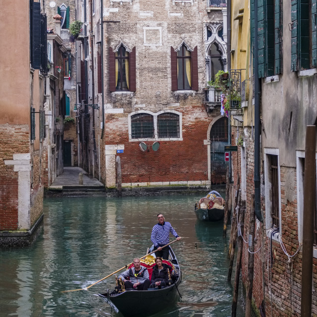 """""""A Gondola, the traditional venetian rowing boat, is cruising on a small canal between the ailing brick houses of the so-called 'Floating city'"""" stock image"""