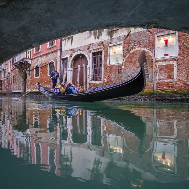"""""""A Gondola, the traditional venetian rowing boat, is cruising on a small canal between the ailing brick houses of the swimming town, passing a stone arch bridge"""" stock image"""